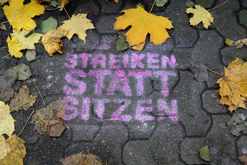 STRIKE INSTEAD OF SIT Autumn Leaf Town Street Stone Concrete Brown Yellow Gray Might Brave Determination Attachment Graffiti Lanes & trails street scene Slogan