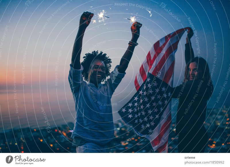 Happy mixed race Couple celebrating with sparkler and USA flag Human being Vacation & Travel Youth (Young adults) Summer Young woman Young man Joy 18 - 30 years