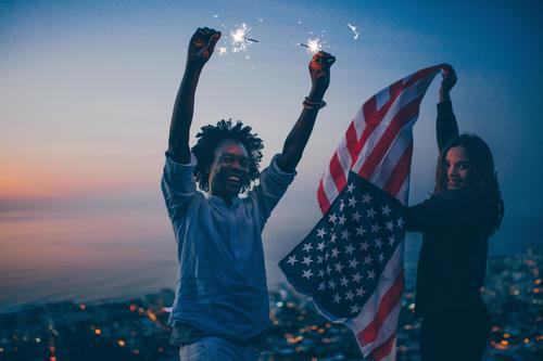 Happy mixed race Couple celebrating with sparkler and USA flag Lifestyle Joy Vacation & Travel Tourism Trip Adventure Freedom Summer Night life Party