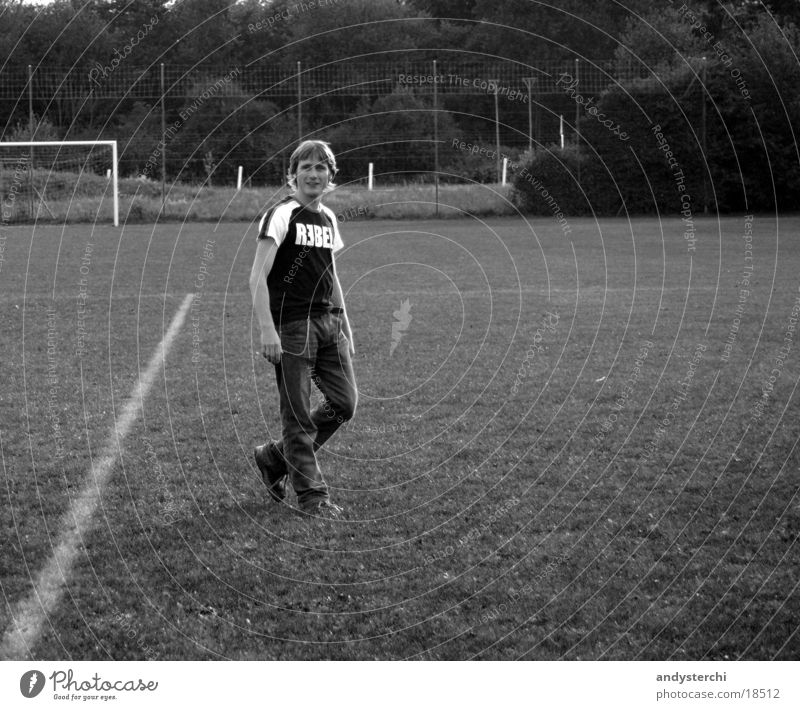 REBEL Football pitch Meadow Stand Blonde Man rebel T-shirt Black & white photo Cool (slang) Gate Signs and labeling crossed legs