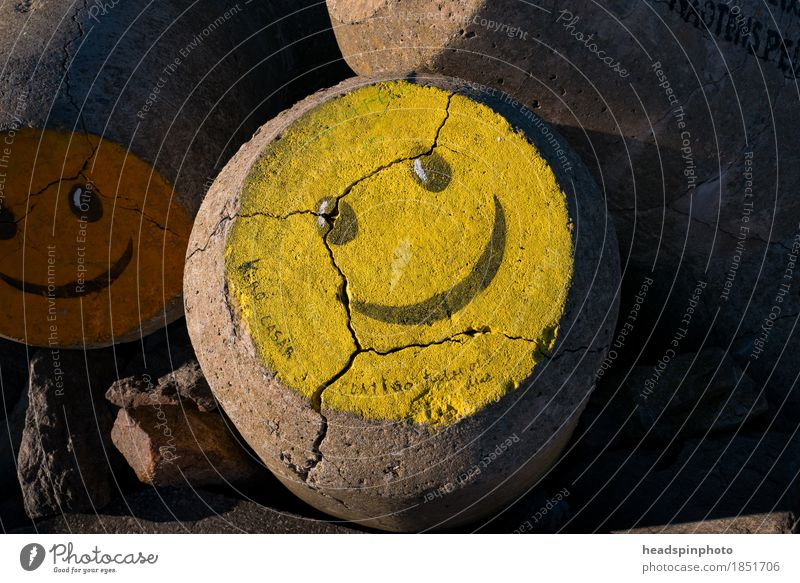 Yellow smiley on a water breaker in Aveiro, Portugal Vacation & Travel Tourism Beach Ocean Waves Work of art Painting and drawing (object) Stone Sign Graffiti
