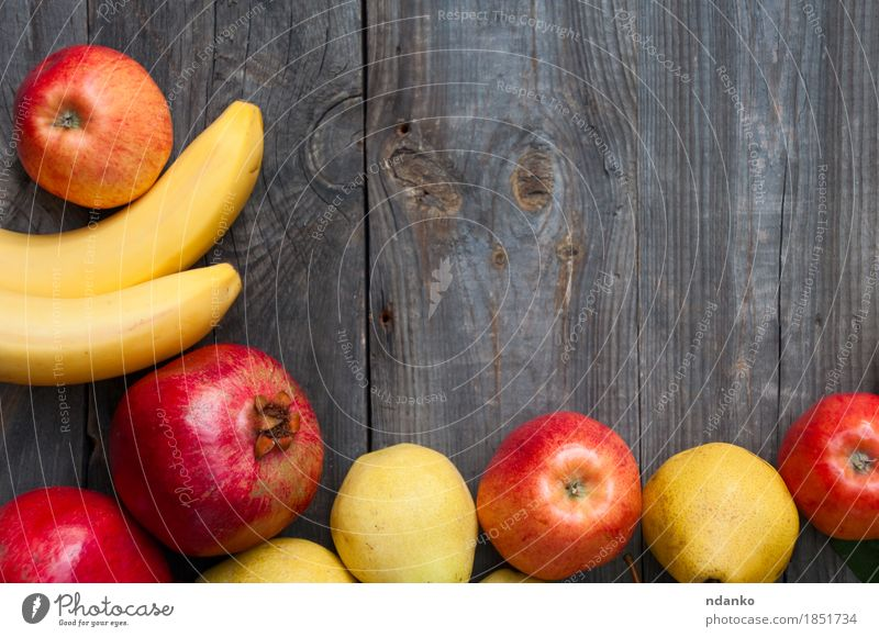 fruit on wooden background: banana, apple, pear and pomegranate Autumn Lifestyle Wood Food Gray Fruit Fresh Vantage point Apple Top Vegetarian diet Horizontal Juicy Raw Banana Pear