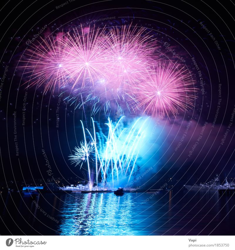 Blue colorful fireworks on the black sky Sky Christmas & Advent Colour Water White Red Joy Dark Black Art Freedom Feasts & Celebrations Party Lake Pink