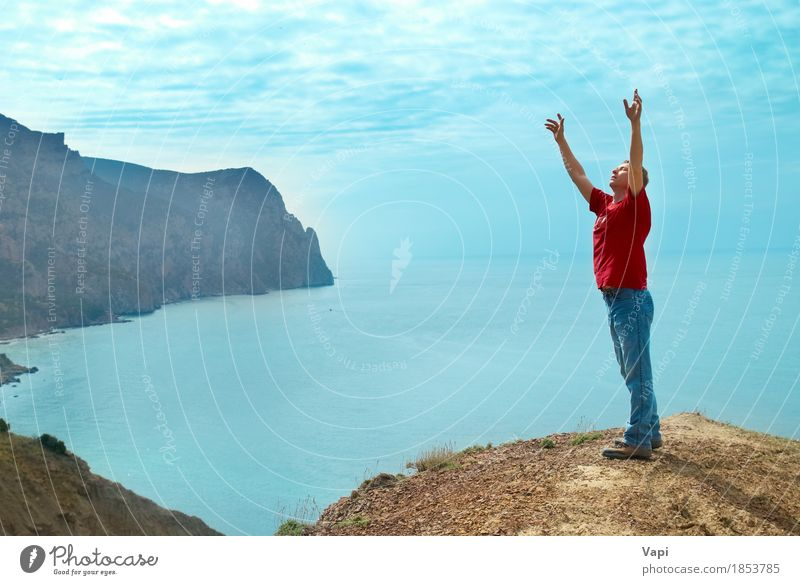Happy man standing on the cliff with hands up Human being Sky Nature Vacation & Travel Youth (Young adults) Man Blue Summer Water White Sun Young man Ocean Hand