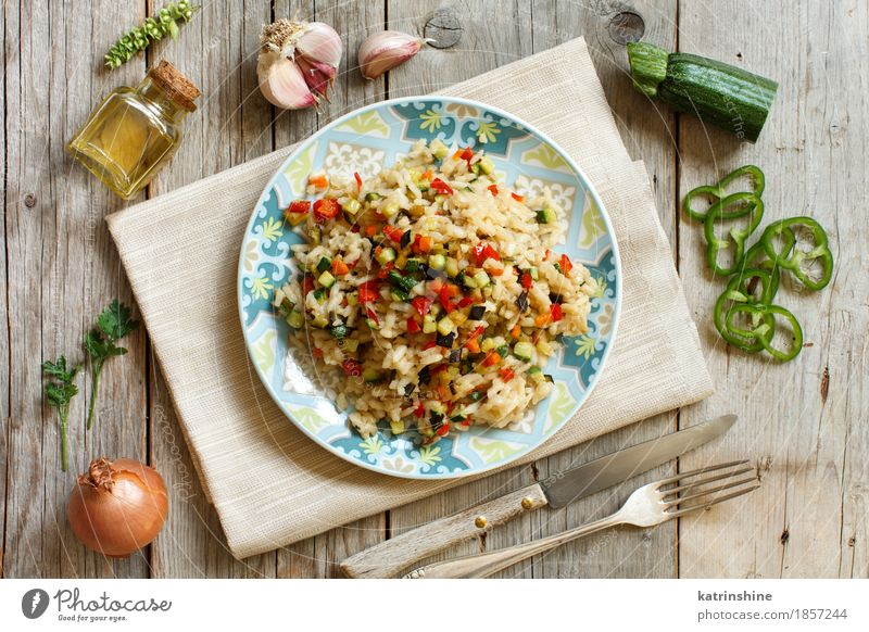Risotto with vegetables on a wooden table Vegetable Grain Herbs and spices Cooking oil Nutrition Lunch Dinner Vegetarian diet Diet Italian Food Plate Bottle