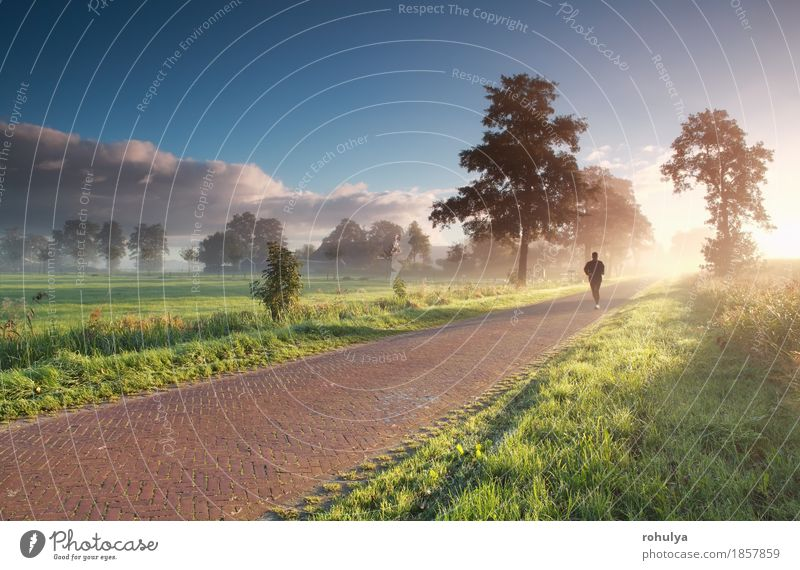 runner in countryside during misty summer sunrise Human being Sky Nature Man Blue Summer Green Sun Landscape Adults Street Meadow Lanes & trails Movement Sports