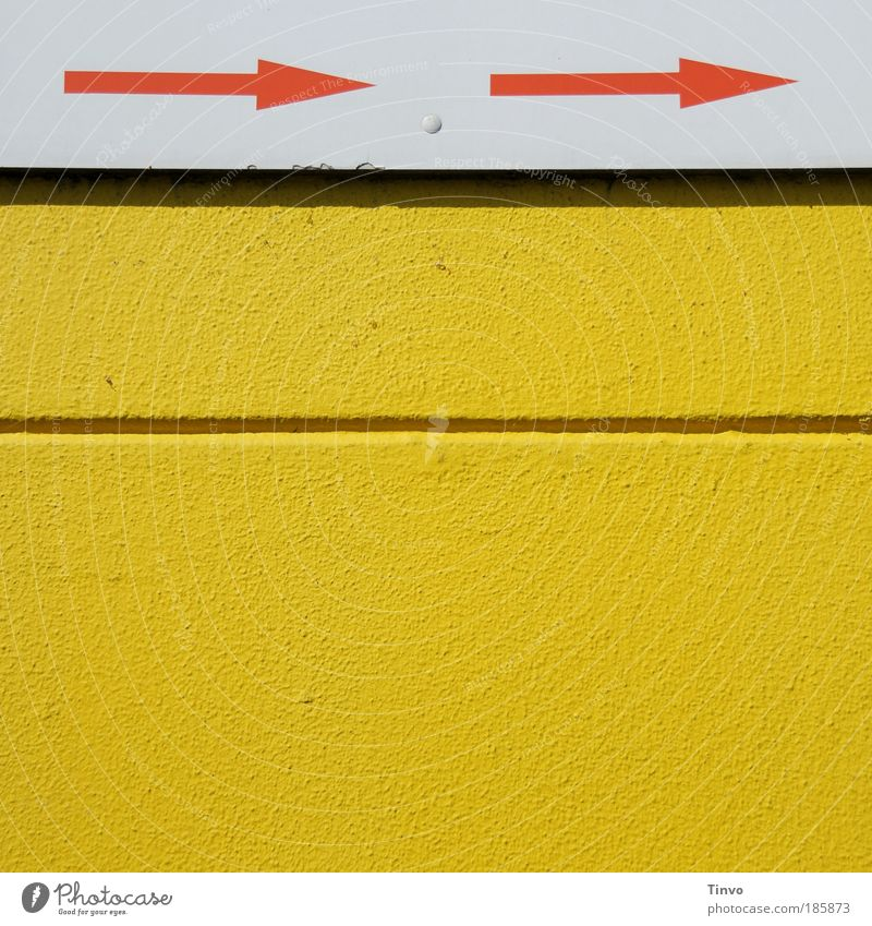 -> . -> Wall (barrier) Wall (building) Yellow Red White Graphic Arrow Signs and labeling Direction Trend-setting Furrow exterior wall Colour photo Exterior shot