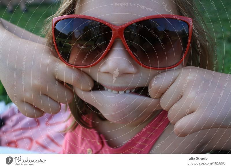 Show me your teeth. Human being Feminine Child Girl Infancy 1 Nature Summer Beautiful weather Grass Meadow T-shirt Sunglasses Brunette Short-haired Smiling Sit