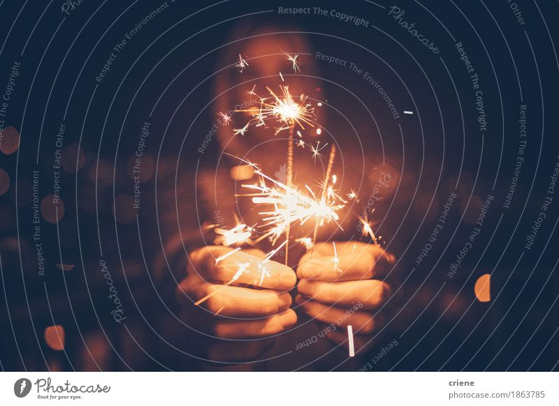 Man holding sparklers in his hands celebrating new years eve Man Christmas & Advent Hand Adults Lifestyle Feasts & Celebrations Party Decoration Gold Birthday Happiness Illuminate Event New Year's Eve Night life Entertainment