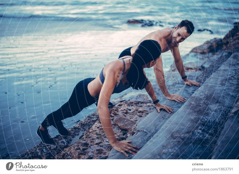 Young fit adult couple doing push up's together on staircas Lifestyle Wellness Leisure and hobbies Beach Ocean Sports Fitness Sports Training Sportsperson