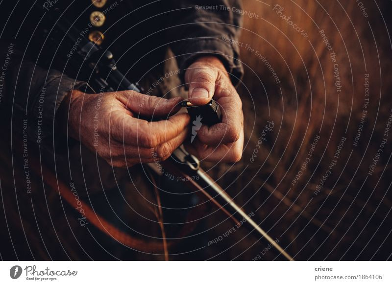 Close up of hunter loading his shotgun with bullets Nature Man Hand Adults Environment Warmth Senior citizen Sports Wild Leisure and hobbies Field Protection Male senior Hunting Weapon Hunter