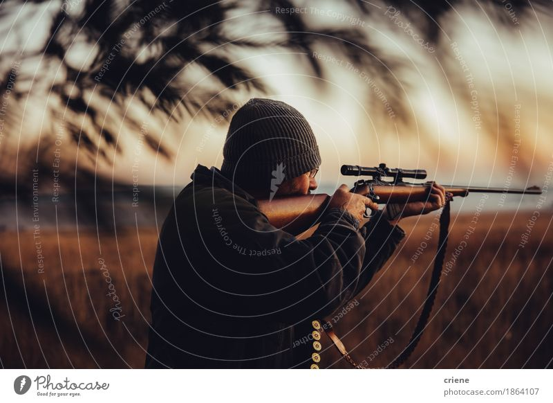 hunter observing on field and pointing gun to his prey Lifestyle Leisure and hobbies Hunting Man Adults Male senior Senior citizen Arm 45 - 60 years