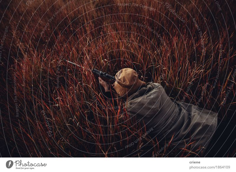 High angle view of Hunter laying in high red grass Nature Man Landscape Red Adults Lifestyle Sports Grass Wild Leisure and hobbies Copy Space Lie To enjoy Indicate Passion Hunting