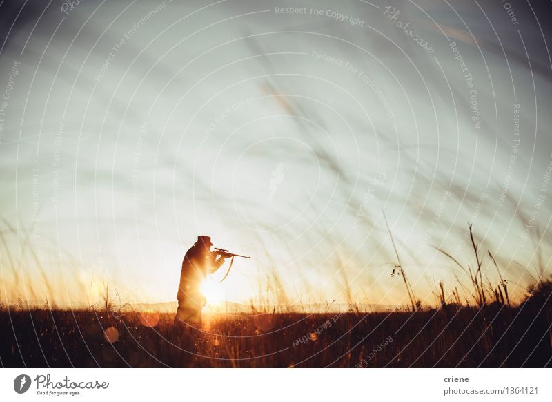 Hunter loading sniper and shooting prey in long grass in sunrise Nature Man Animal Adults Senior citizen Meadow Lifestyle Grass Leisure and hobbies Copy Space
