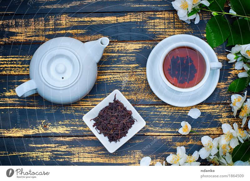 Black tea in a white cup and saucer and jasmine flowers Herbs and spices Breakfast Tea Table Plant Flower Leaf Wood Fresh Hot Brown Yellow Green White branch
