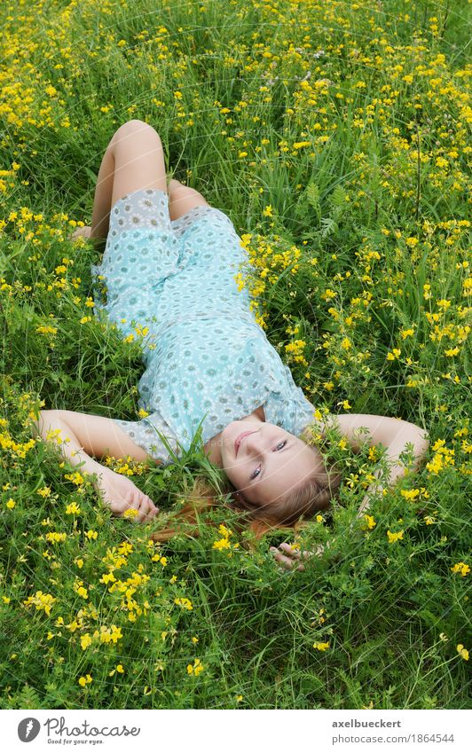 young woman lies upside down on a flower meadow Lifestyle Joy Contentment Relaxation Leisure and hobbies Human being Feminine Girl Young woman