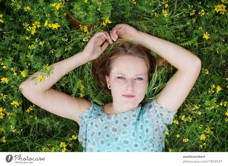 young woman lies on a flower meadow Lifestyle Well-being Contentment Relaxation Leisure and hobbies Summer Human being Feminine Young woman Youth (Young adults)