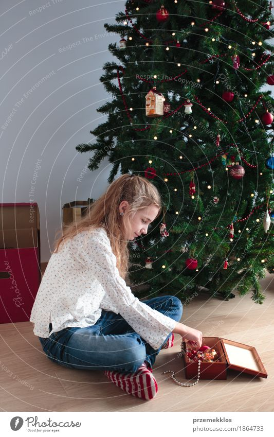 Young girl decorating Christmas tree at home Human being Child Christmas & Advent Tree Joy Girl Lifestyle Feasts & Celebrations Decoration Infancy 8 - 13 years Tradition Home Pine Ornament