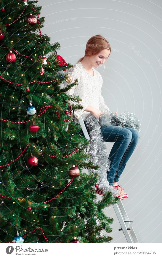 Young girl unwrapping Christmas decoration sitting on a ladder Human being Child Christmas & Advent Tree Joy Girl Lifestyle Feasts & Celebrations Decoration