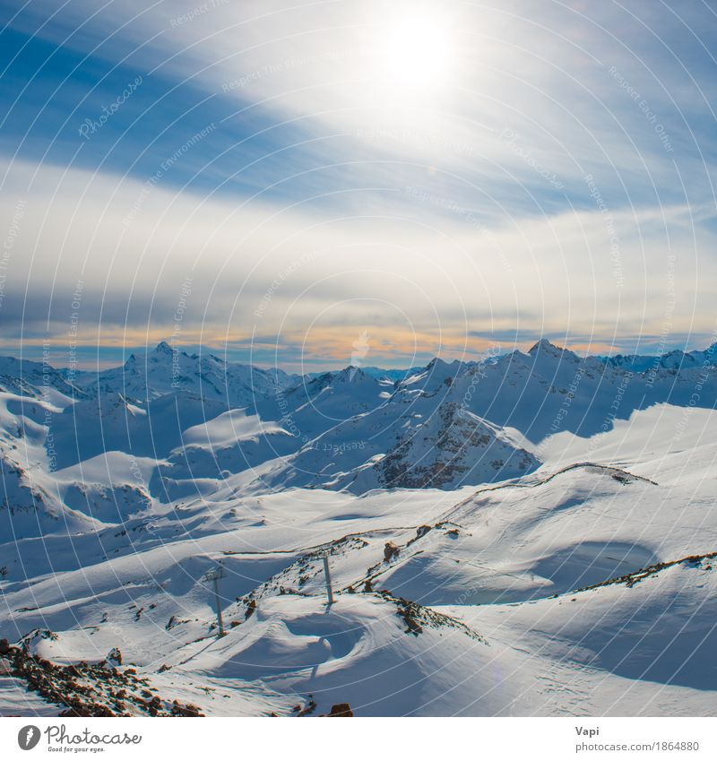 Snowy blue mountains in clouds at sunset Sky Nature Vacation & Travel Blue White Sun Landscape Clouds Winter Mountain Black Yellow Sports Snow Rock Tourism