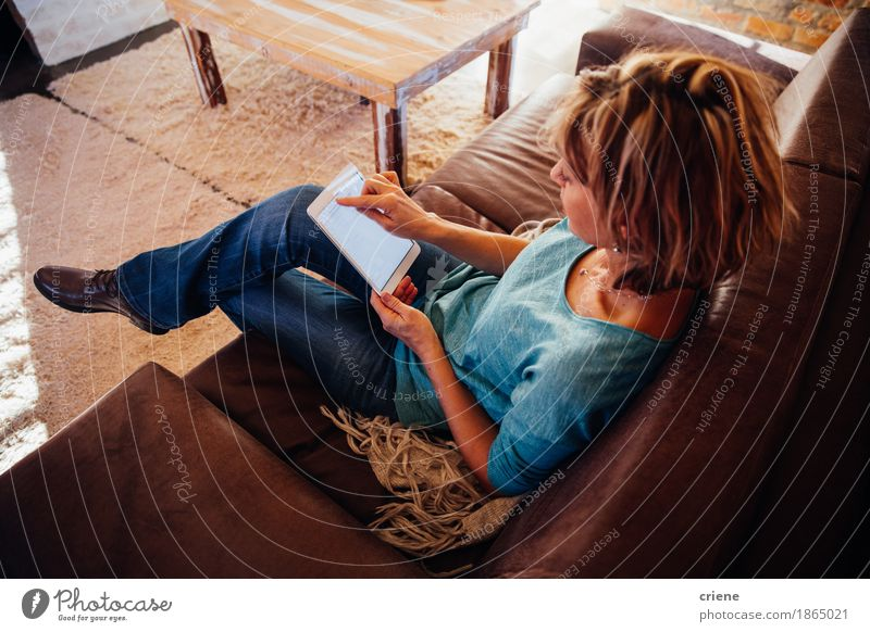 mature woman sitting on sofa using digital tablet Woman House (Residential Structure) Adults Lifestyle Business Office Modern Technology Telecommunications Computer Reading Female senior Internet Home Newspaper Living room