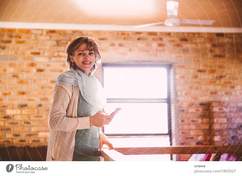 Mature woman smiling at camera while holding smartphone Woman Joy Adults Lifestyle Business Flat (apartment) Living or residing Copy Space Office Modern Technology 45 - 60 years Telecommunications Smiling Female senior Telephone