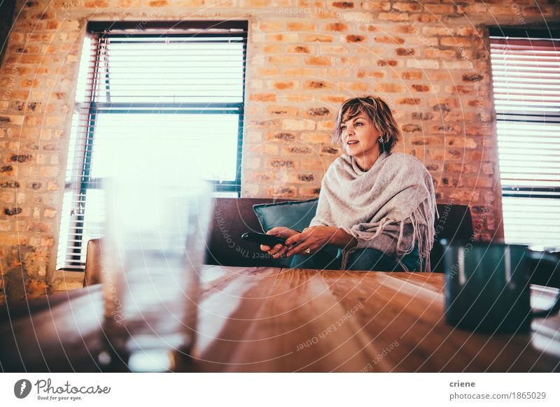 Mature woman watching TV at home sitting on couch Lifestyle Joy Leisure and hobbies Living or residing Flat (apartment) House (Residential Structure)
