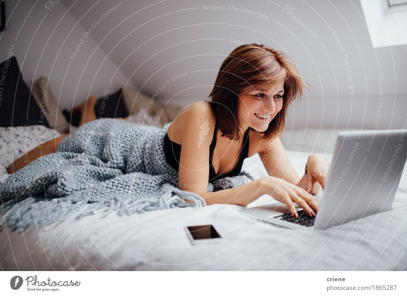 Young caucasian women laying in bed with laptop Youth (Young adults) Young woman Joy Lifestyle Business Work and employment Flat (apartment) Living or residing Modern Communicate Computer Study Smiling Telephone Education University & College student