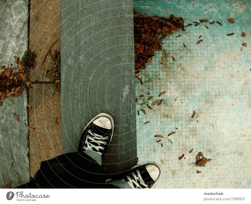 seasonal chaos Man Adults Loneliness Chucks Pattern Ground Asphalt Floor covering Leaf Autumn Stand Denim Corner Line Trashy Colour photo Subdued colour