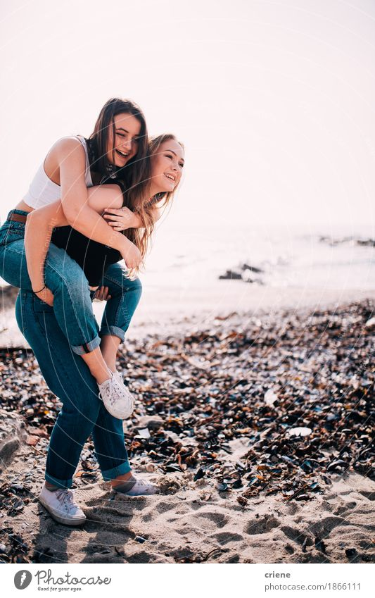 Happy Caucasian Teenage girls doing piggy back on the beach Human being Youth (Young adults) Summer Young woman Ocean Joy Girl Lifestyle Coast Laughter Couple Tourism Together Friendship Smiling Cute