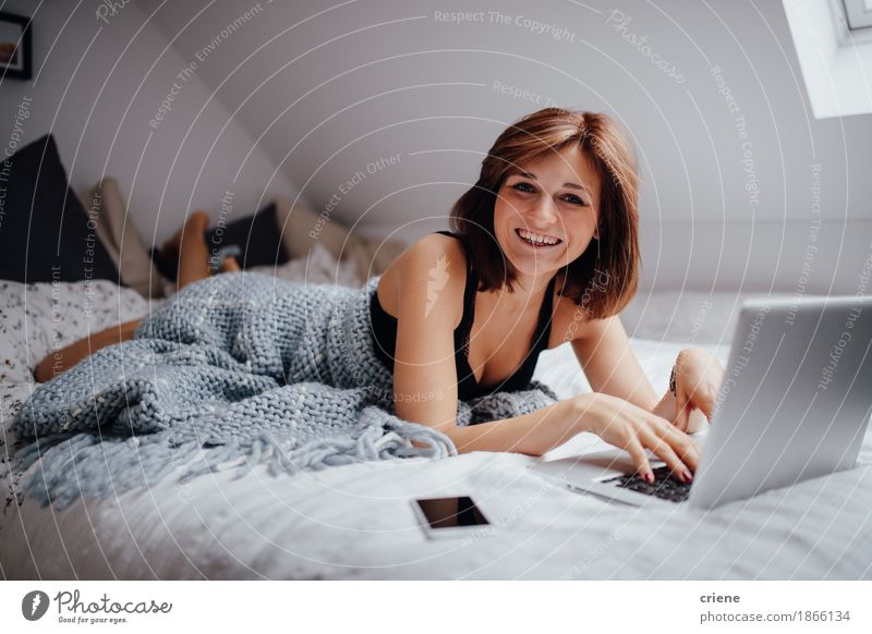 Young caucasian women lying in bed with laptop smiling Human being Youth (Young adults) Beautiful Young woman Joy 18 - 30 years Adults To talk Lifestyle