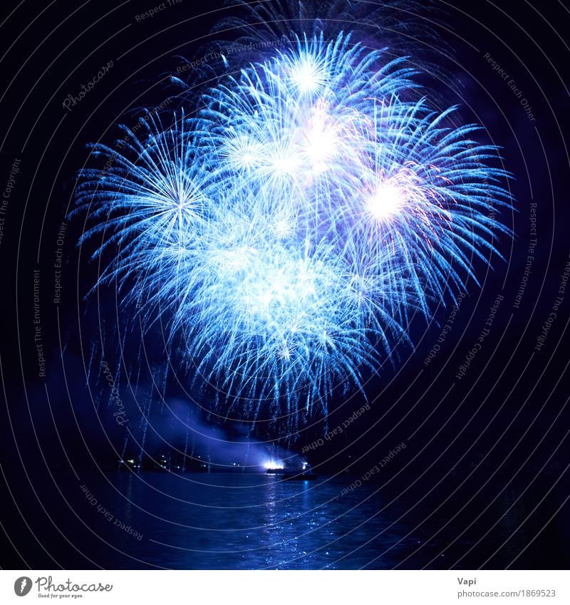 Blue fireworks on the black sky Sky Christmas & Advent Colour Water White Red Joy Dark Black Art Freedom Feasts & Celebrations Party Lake Bright