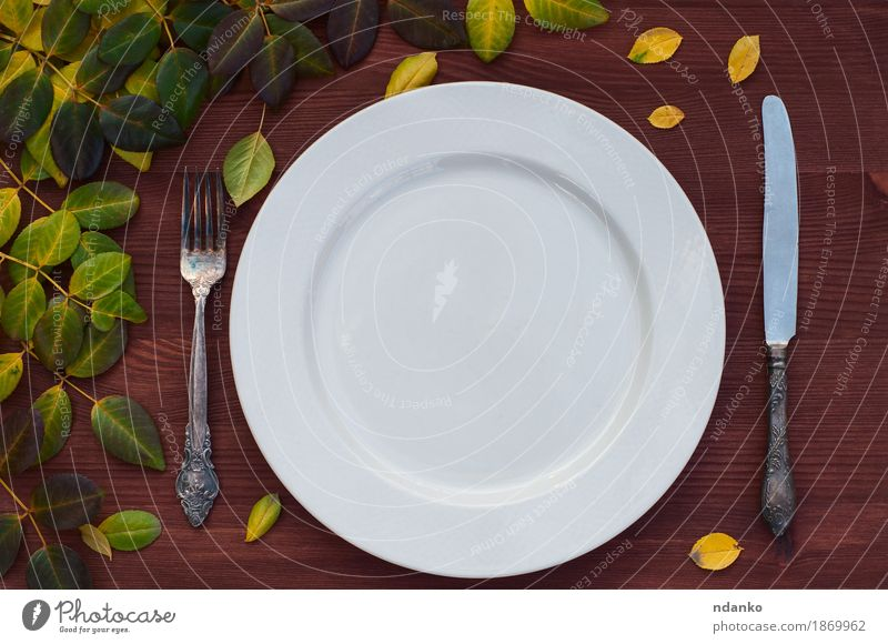 Empty white plate, knife and fork on brown wood surface Lunch Plate Knives Fork Table Kitchen Restaurant Leaf Metal Brown White empty table setting twig ceramic
