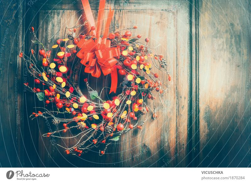 Christmas wreath on wooden door with red ribbon, berries and bokeh Style Design Winter Living or residing Interior design Decoration Feasts & Celebrations