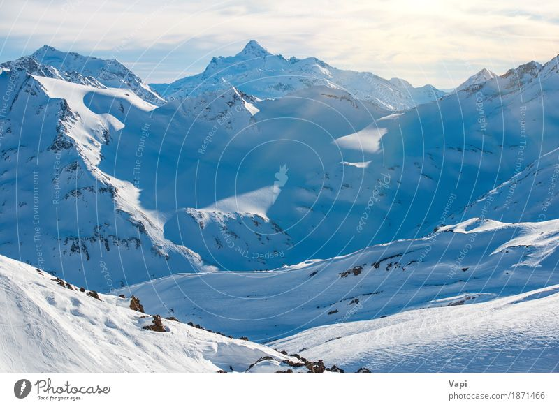 Snowy blue mountains in clouds Sky Nature Vacation & Travel Blue White Landscape Clouds Winter Mountain Black Yellow Rock Tourism Ice Action