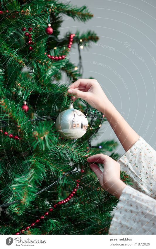 Young girl decorating Christmas tree with ball at home Human being Christmas & Advent Tree Hand Joy Girl Lifestyle Feasts & Celebrations Decoration Arm