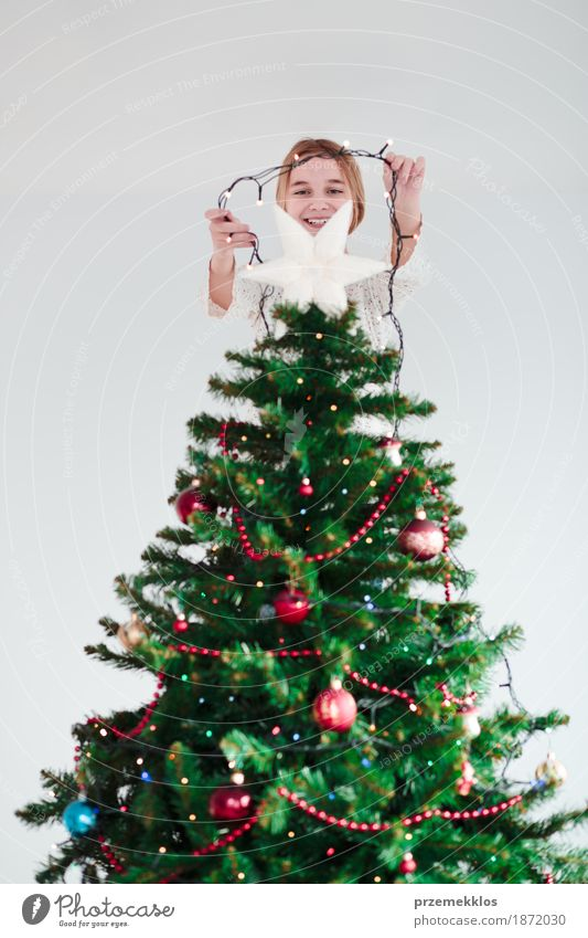 Young girl decorating Christmas tree with lights at home Human being Child Youth (Young adults) Christmas & Advent Tree Joy Girl Lifestyle Feasts & Celebrations