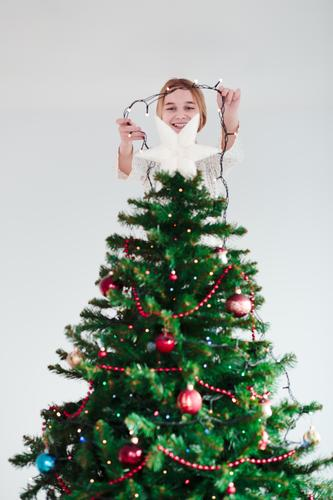 Young girl decorating Christmas tree with lights at home Lifestyle Joy Decoration Feasts & Celebrations Christmas & Advent Human being Girl Youth (Young adults)