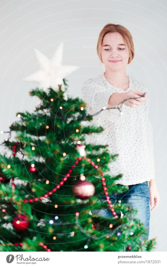 Young girl decorating Christmas tree with lights at home Human being Child Youth (Young adults) Christmas & Advent Tree Joy Girl Lifestyle Feasts & Celebrations Decoration Blonde Infancy Happiness 8 - 13 years Tradition Home