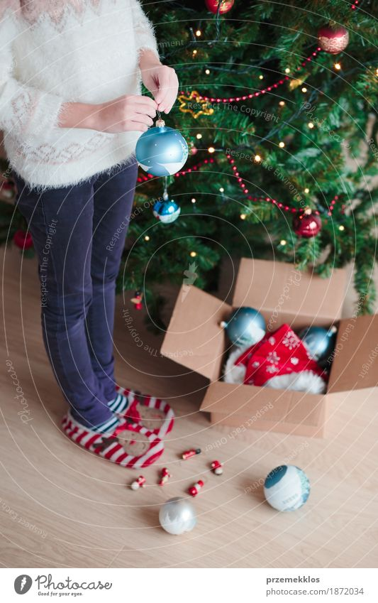 Young girl decorating Christmas tree at home Human being Child Youth (Young adults) Christmas & Advent Tree Joy Girl Lifestyle Feasts & Celebrations Decoration