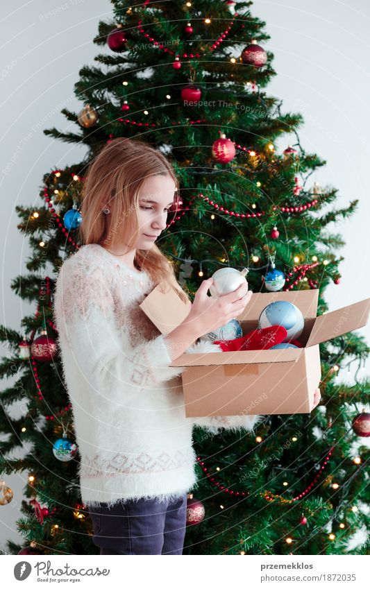 Young girl decorating Christmas tree at home Lifestyle Joy Decoration Feasts & Celebrations Christmas & Advent Human being Girl Youth (Young adults) 1