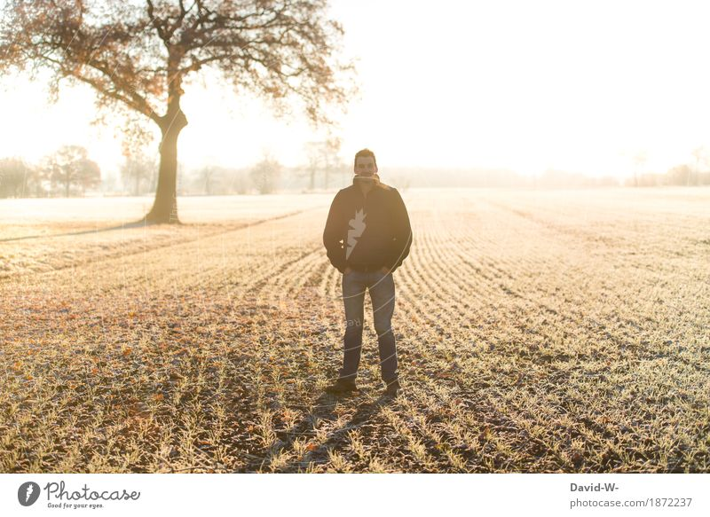 Man stands outside in the field in frost chill Frost Sunlight Sunbeam Sunset Light Yellow Arable land acre Frozen hands in the pockets Looking into the camera
