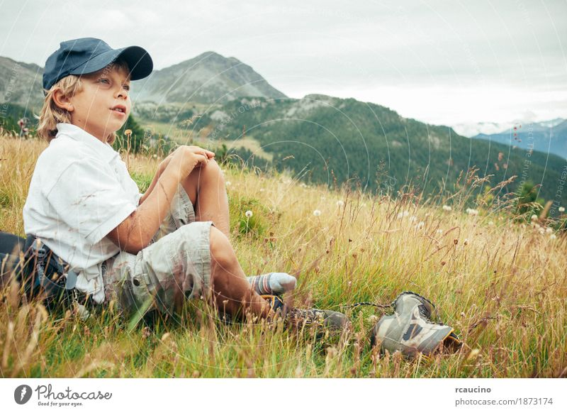 Young boy takes a rest in a meadow during a mountain hike Relaxation Vacation & Travel Tourism Adventure Summer Mountain Hiking Child Boy (child) Nature