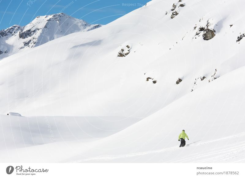 Snowboarder goes downhill over a snowy mountain landscape. Vacation & Travel Winter Mountain Sports Boy (child) Sky Alps Freeze Speed cold Extreme Resort