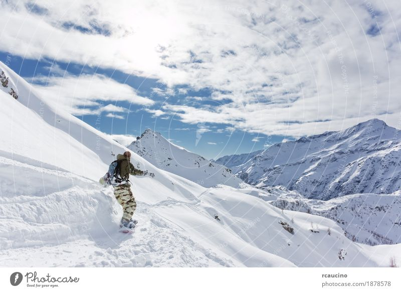 Snowboarder goes downhill over a snowy mountain landscape Vacation & Travel Tourism Winter Mountain Sports Skiing Ski run Boy (child) 1 Human being Landscape