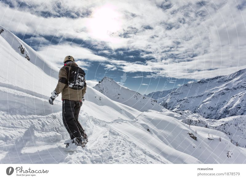 Snowboarder goes downhill over a snowy mountain landscape. Vacation & Travel Winter Mountain Sports Skiing Boy (child) Landscape Sky Alps Freeze Speed Clear sky