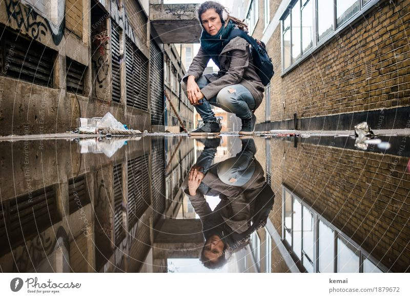 Woman with headphones in side alley in front of puddle in squat Lifestyle Well-being Calm Leisure and hobbies Vacation & Travel Trip Adventure Freedom City trip