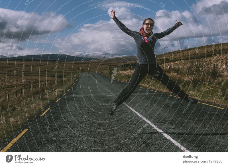 jumping woman on a country road with mountains in the background Feminine Young woman Youth (Young adults) 1 Human being 18 - 30 years Adults Landscape Clouds