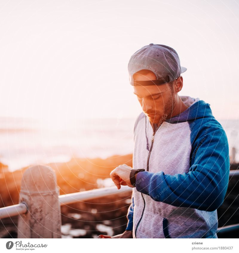 young adult man checking notification on his smart watch Youth (Young adults) Man Young man 18 - 30 years Adults Fashion Clock Modern Technology Telecommunications Computer Observe Cool (slang) Internet Information Technology Cap