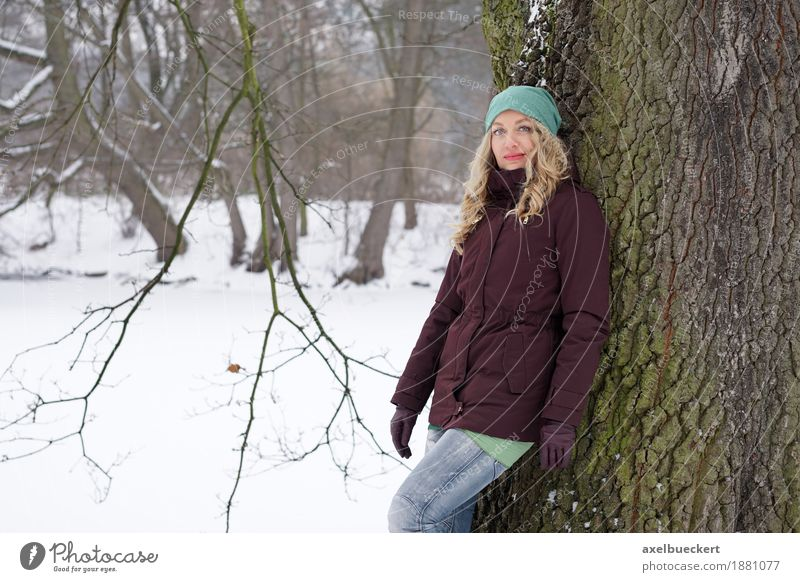 woman leaning against tree in winter landscape Lifestyle Winter Snow Human being Feminine Woman Adults 1 30 - 45 years Nature Tree Park Forest Fashion Jeans